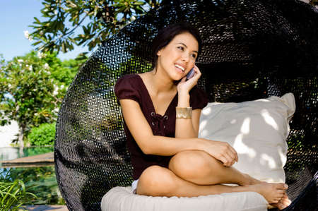An attractive young woman talking on her mobile phone outdoors photo