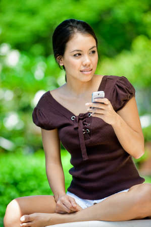 An attractive young woman using her mobile phone outdoors photo