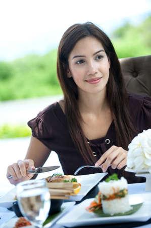 Eine attraktive caucasian Frau haben eine entspannte mahlzeit outdoors