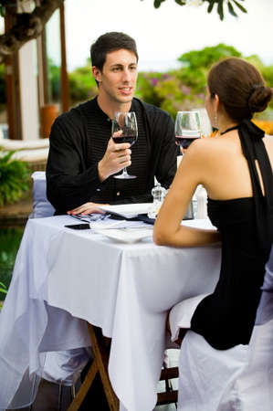 An attractive caucasian couple having a formal meal with red wine outdoors photo