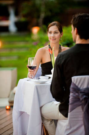 An attractive caucasian couple having a formal meal outdoors photo