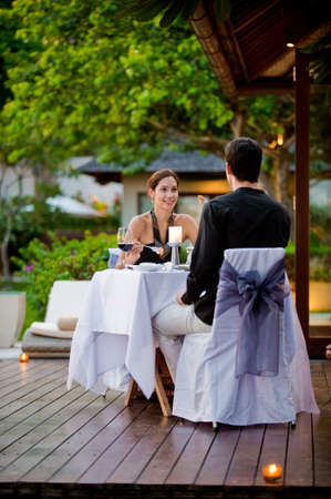 An attractive caucasian couple having a formal meal outdoors