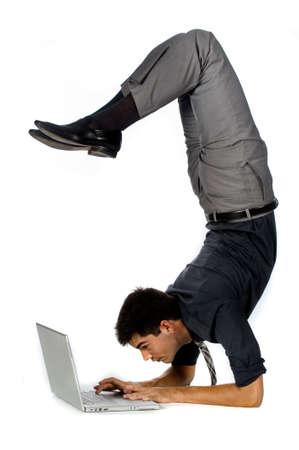 Eine attraktive sportlich Geschäftsmann, die einen Handstand zu tun, während mit seinem Laptop gegen weißen Hintergrund  Lizenzfreie Bilder