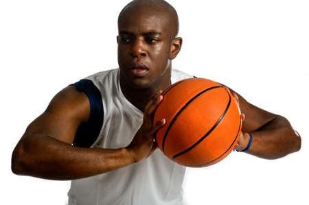 An attractive athletic man playing basketball against white background