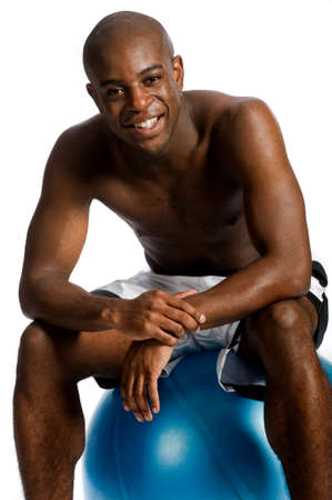 An attractive athletic man sitting on a fitness ball against white background photo