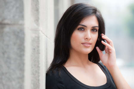A young attractive woman standing outside with phone Standard-Bild