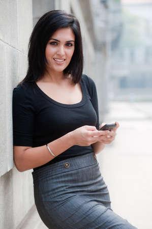 Eine junge, attraktive Frau stehend außerhalb mit Telefon