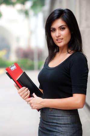 Eine schöne young Businesswoman standing außerhalb holding Dateien und notebook