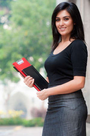 adult indian: A beautiful young businesswoman standing outside holding files and notebook Stock Photo