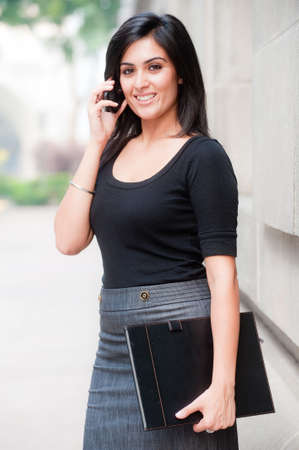 A young attractive Asian businesswoman standing outside with mobile phone Standard-Bild