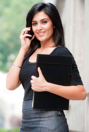 businesswoman: A young attractive Asian businesswoman standing outside with mobile phone Stock Photo