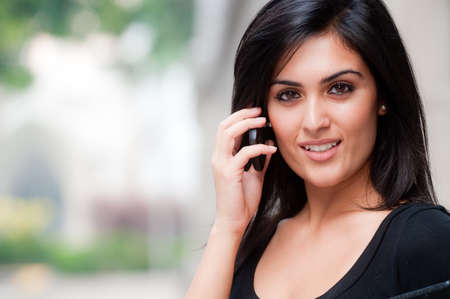 A young attractive Asian businesswoman standing outside with mobile phone photo