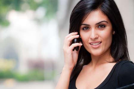 Eine junge attraktive asiatischen geschäftsfrau stehend außerhalb mit Mobiltelefon