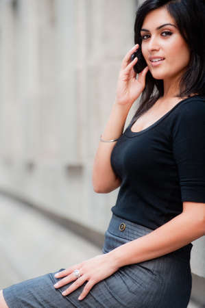 A young attractive Asian businesswoman standing outside with mobile phone Stock Photo - 8179107