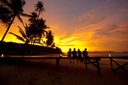 Four friends sitting on a jetty on a tropical island enjoying drinks at sunset Stock Photo