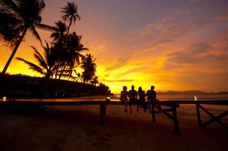Four friends sitting on a jetty on a tropical island enjoying drinks at sunset Standard-Bild