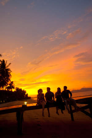 Four friends sitting on a jetty on a tropical island enjoying drinks at sunset photo