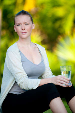 An attractive young woman sitting outside holding a glass of water Stock Photo - 9379840