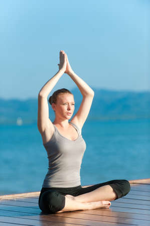 An attractive young woman doing yoga on a jetty by the sea Stock Photo - 9379842