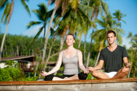 An attractive young woman and man doing yoga on a jetty with a tropical island villa behind Stock Photo - 9379848