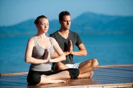 Eine attraktive junge Frau und Mann tun Yoga auf einer Mole mit dem blauen Meer und eine andere Insel hinter Ihnen Lizenzfreie Bilder