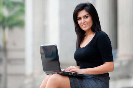 A young attractive Asian businesswoman sitting outside with laptop Stock Photo