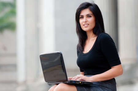 A young attractive Asian businesswoman sitting outside with laptop photo