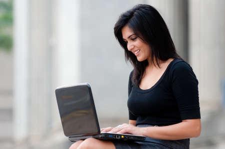 Eine junge attraktiv asiatischen Geschäftsfrau sitzt außerhalb mit laptop