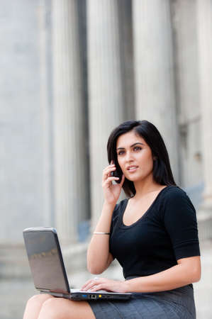 A young attractive Asian businesswoman sitting outside with laptop and phone photo