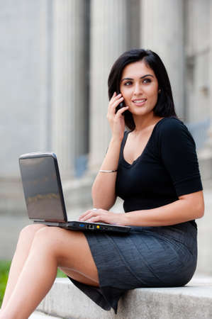 businesswoman skirt: A young attractive Asian businesswoman sitting outside with laptop and phone