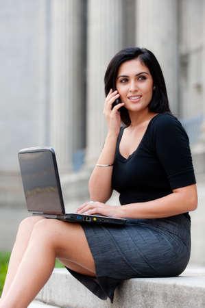 Eine junge attraktive asiatischen geschäftsfrau sitzen außerhalb mit Laptop und Handy