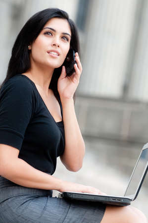 An attractive Indian businesswoman sitting outside with laptop and phone photo