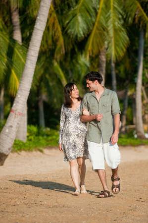 sandal tree: Una joven pareja caminando por una playa arbolada