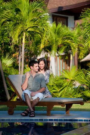 A young couple sitting together on a pool lounger outside by the pool photo