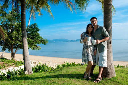 A young couple on vacation standing outside by beach with cups of coffee Stock Photo - 9404647