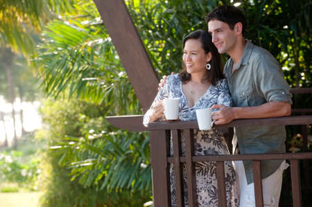A young couple on vacation standing on the balcony holding mugs Stock Photo