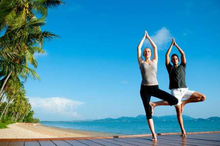 Een aantrekkelijke jonge vrouw en de man doet yoga op een aanlegsteiger met de blauwe oceaan en een ander eiland achter hen