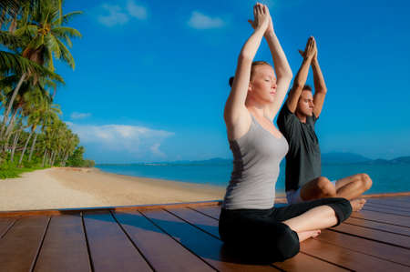 An attractive young woman and man doing yoga on a jetty with the blue ocean and another island behind them Stock Photo