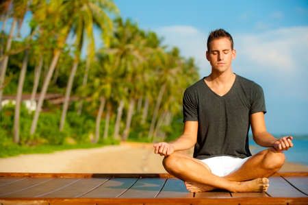 man meditating: A good-looking young  man doing yoga on a jetty with tropical island backdrop Stock Photo