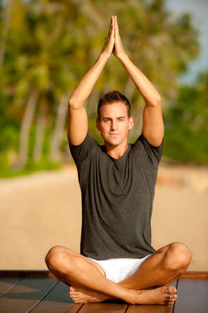 yoga outside: A good-looking young  man doing yoga on a jetty with tropical island backdrop Stock Photo