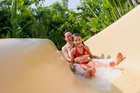 Mother and daughter sliding down the water slide Stock Photo