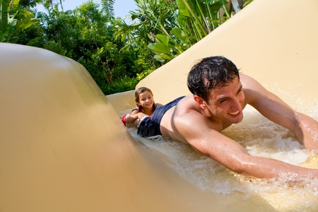 Father and daughter sliding down the water slide