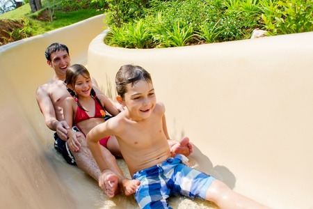 Young and attractive Family of three sliding down the water slide. Stock Photo