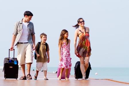 Une famille de 4 arrivant au Centre de villégiature avec leurs bagages. Banque d'images
