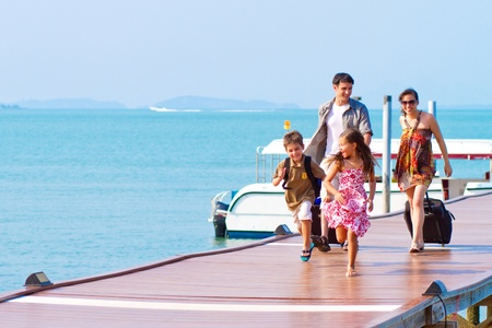 A family of 4 arriving at the resort with their luggages. Stock Photo