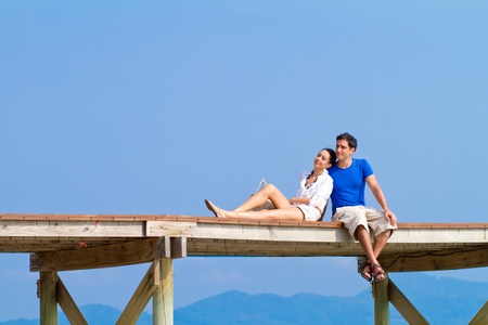 Front view of a couple sitting at the edge of a wooden boardwalk of a harbour Standard-Bild