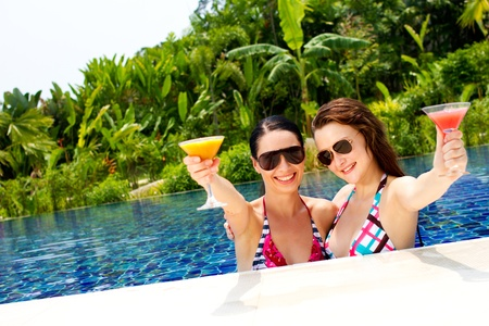 Two beautiful women enjoying their summer vacation with cocktails by the pool