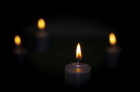 burning candles, dark background, close up on the flame