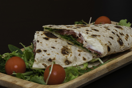 italian piadina, with salad, ham, cheese, mozzarella and tomatoes, wood dish and black background