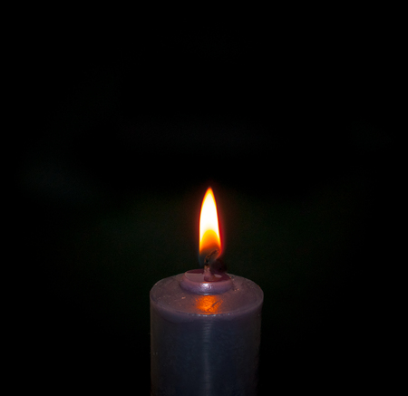single candle, dark background, close up on the flame